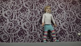 Λίγο ευτυχές παιδί που περπατά και που χορεύει στον καναπέ και τη μουσική ακούσματος o απόθεμα βίντεο