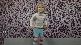 Λίγο ευτυχές παιδί που πηδά και που χορεύει στον καναπέ και τη μουσική ακούσματος o απόθεμα βίντεο