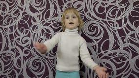 Λίγο ευτυχές παιδί που χορεύει στον καναπέ και τη μουσική ακούσματος στο σπίτι o φιλμ μικρού μήκους