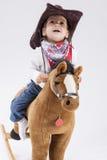 Λίγο εύθυμο καυκάσιο κορίτσι στο άλογο παιχνιδιών οδήγησης ιματισμού Cowgirl Στοκ εικόνα με δικαίωμα ελεύθερης χρήσης