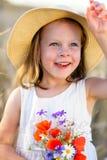 Λίγο εύθυμο κορίτσι σε ένα καπέλο αχύρου με την άγρια ανθοδέσμη παπαρουνών λουλουδιών κόκκινη Στοκ φωτογραφία με δικαίωμα ελεύθερης χρήσης
