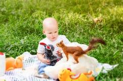 Λίγο ελατήριο παιδιών στο πάρκο κοιτάζει καταπληκτικά στο θρασύ σκίουρο Στοκ Εικόνες