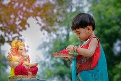 Λίγο ινδικό παιδί κοριτσιών με το ganesha και την επίκληση Λόρδου, ινδικό φεστιβάλ ganesh στοκ εικόνες