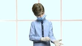 Λίγο καυκάσιο αγόρι βάζει στα λαστιχένια γάντια απόθεμα βίντεο