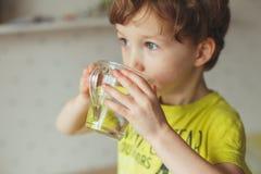 Λίγο καυκάσιο αγόρι πίνει το νερό στο ποτήρι στο σπίτι Το χαριτωμένο σγουρό μικρό παιδί είναι πόσιμο νερό Υγεία και έννοια νερού Στοκ Εικόνα