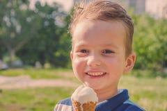 Λίγο καυκάσιο αγόρι που απολαμβάνει ένα λειώνοντας παγωτό μια sweltering καυτή θερινή ημέρα Πράσινα θερινά δέντρα στο υπόβαθρο στοκ φωτογραφίες