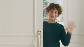 Λίγο καυκάσιο αγόρι που εισάγει το κυματίζοντας χέρι δωματίων απόθεμα βίντεο