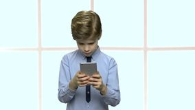 Λίγο καυκάσιο αγόρι που χρησιμοποιεί το smartphone φιλμ μικρού μήκους