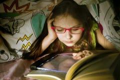 Λίγο καυκάσιο κορίτσι που διαβάζει ένα βιβλίο κάτω από το coverlet Στοκ Εικόνα