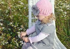 Λίγο καυκάσιο κορίτσι στην καρέκλα στα wildflowers Στοκ εικόνα με δικαίωμα ελεύθερης χρήσης