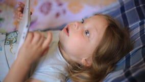 Λίγο καυκάσιο 2χρονο κορίτσι που βρίσκεται στα κινούμενα σχέδια καρό μαξιλαριών και προσοχής σε έναν υπολογιστή ταμπλετών σύγχρον απόθεμα βίντεο