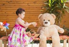 Λίγο καλό παιδί που μοιράζεται τα μήλα με το Teddy της αντέχει το φίλο στοκ φωτογραφίες με δικαίωμα ελεύθερης χρήσης