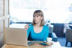 Λίγο κομμάτι! Το πορτρέτο του ελκυστικού νέου κοριτσιού με την ξανθή τρίχα στην μπλε μπλούζα κάθεται στον καφέ, λειτουργεί και κά στοκ εικόνες