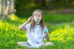 Λίγο κορίτσι κώλων που φυσά βράζει καθμένος στη χλόη Στοκ εικόνα με δικαίωμα ελεύθερης χρήσης