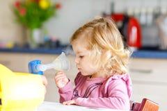 Λίγο κορίτσι μικρών παιδιών που κάνει την εισπνοή με nebulizer στο σπίτι Πατέρας ή μητέρα που βοηθά και που κρατά τη συσκευή Παιδ στοκ φωτογραφία με δικαίωμα ελεύθερης χρήσης