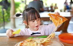 Λίγο κορίτσι παιδιών απολαμβάνει την πίτσα στοκ φωτογραφίες με δικαίωμα ελεύθερης χρήσης