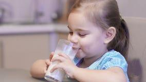 Λίγο κορίτσι παιδιών που πίνει ένα γάλα απόθεμα βίντεο