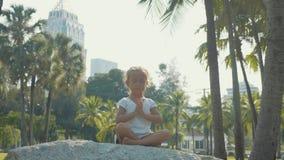 Λίγο κορίτσι παιδιών που στο όμορφο πάρκο με τους φοίνικες στο υπόβαθρο φιλμ μικρού μήκους