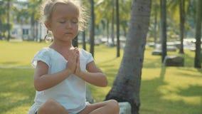 Λίγο κορίτσι παιδιών που στο όμορφο πάρκο με τους φοίνικες στο υπόβαθρο απόθεμα βίντεο