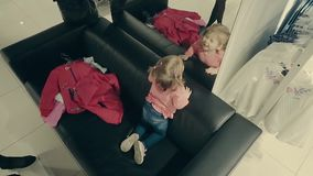 Λίγο κορίτσι παιδιών σε ένα κατάστημα ιματισμού κάθεται στον καναπέ μπροστά από έναν καθρέφτη απόθεμα βίντεο