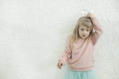 Λίγο κορίτσι πριγκηπισσών που κάνει τα πρόσωπα διασκέδασης στον άσπρο τουβλότοιχο backgtound Στοκ φωτογραφίες με δικαίωμα ελεύθερης χρήσης