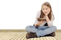 Λίγο κορίτσι σπουδαστών που μελετά και που διαβάζει το βιβλίο στο σχολείο Στοκ Φωτογραφία