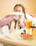 Λίγο κορίτσι brunette που βρίσκεται στο κρεβάτι και τη φυσώντας μύτη στον ιστό Στοκ Φωτογραφίες