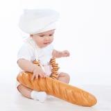 Λίγο κοριτσάκι αρτοποιών με μια μακριά φραντζόλα και bagels Στοκ εικόνα με δικαίωμα ελεύθερης χρήσης