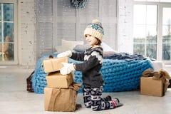 Λίγο κοριτσάκι διπλώνει επάνω ένα βουνό των κιβωτίων δώρων στο σπίτι, κοντά στο κρεβάτι Το εσωτερικό είναι διακοσμημένο με το ντε Στοκ Φωτογραφία