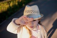 Λίγο κοριτσάκι εξετάζει επάνω από κάτω από το καπέλο του τη κάμερα Στοκ φωτογραφία με δικαίωμα ελεύθερης χρήσης