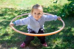Λίγο κοριτσάκι μαθαίνει να εξετάζει hulahup Το παιδί κρατά τη στεφάνη με δύο χέρια στοκ εικόνα με δικαίωμα ελεύθερης χρήσης