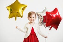 Λίγο κοριτσάκι με τα ζωηρόχρωμα λαμπρά μπαλόνια φύλλων αλουμινίου ενάντια σε ένα wh Στοκ Εικόνες
