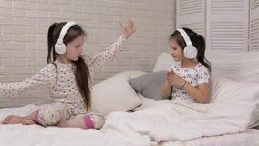 Λίγο κοριτσάκι παιδιών που ακούει τη μουσική με τα ακουστικά φιλμ μικρού μήκους