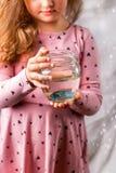 Λίγο κοριτσάκι που κρατά ένα fishbowl με ένα μπλε ψάρι Conce προσοχής Στοκ Εικόνα