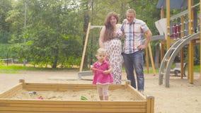 Λίγο κοριτσάκι που παίζει στο Sandbox στην παιδική χαρά απόθεμα βίντεο