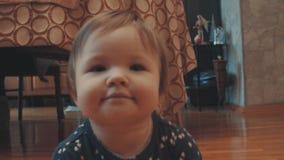 Λίγο κοριτσάκι που σέρνεται, που χαμογελά και που κυματίζει τα χέρια της απόθεμα βίντεο