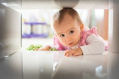 Λίγο κοριτσάκι σέρνεται στο σφιχτό διάστημα στο πλαίσιο του τραπεζάκι σαλονιού στοκ φωτογραφία με δικαίωμα ελεύθερης χρήσης