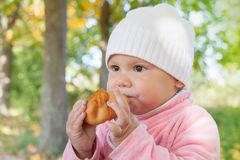 Λίγο κοριτσάκι στο πάρκο φθινοπώρου τρώει τη μικρή πίτα Στοκ εικόνα με δικαίωμα ελεύθερης χρήσης