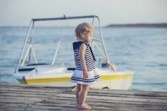 Λίγο κοριτσάκι στο φόρεμα στην ξύλινη αποβάθρα στο υπόβαθρο του θορίου Στοκ φωτογραφίες με δικαίωμα ελεύθερης χρήσης