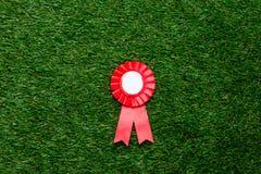 Λίγο κόκκινο βραβείο νικητών στον πράσινο χορτοτάπητα θερινής χλόης Στοκ εικόνα με δικαίωμα ελεύθερης χρήσης