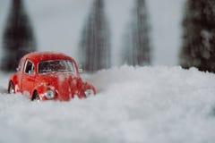 Λίγο κόκκινο παιχνίδι αυτοκινήτων κόλλησε στο χιόνι Στοκ Φωτογραφία