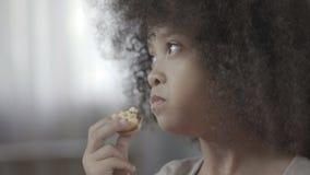 Λίγο μαύρος-μαλλιαρό παιδί που μασά το νόστιμο μπισκότο με την όρεξη, ανθυγειινά τρόφιμα απόθεμα βίντεο