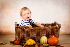 Λίγο μικρό παιδί που παίζει με τα φύλλα και τις κολοκύθες Στοκ φωτογραφία με δικαίωμα ελεύθερης χρήσης