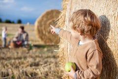 Λίγο μικρό παιδί που τρώει το μήλο με ένα μεγάλο δέμα σανού στο πεδίο Στοκ φωτογραφία με δικαίωμα ελεύθερης χρήσης