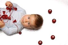 Λίγο μικρό παιδί με την τοποθέτηση στην πλάτη του με τις διακοσμήσεις Χριστουγέννων Στοκ εικόνα με δικαίωμα ελεύθερης χρήσης