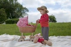 Λίγο μικρό παιδί που παίζει με ένα καροτσάκι υπαίθρια Στοκ εικόνα με δικαίωμα ελεύθερης χρήσης