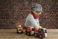 Λίγο μικρό παιδί που παίζει με τα ξύλινα αυτοκίνητα Στοκ Φωτογραφίες