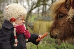 Λίγο μικρό παιδί που ταΐζει ένα πόνι Στοκ φωτογραφία με δικαίωμα ελεύθερης χρήσης