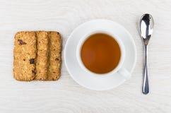 Λίγο μπισκότο-muesli, φλυτζάνι του τσαγιού στο πιατάκι, κουταλάκι του γλυκού Στοκ Φωτογραφία
