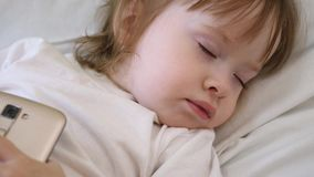Λίγο μωρό έπεσε κοιμισμένο στο μαξιλάρι με το τηλέφωνο στο χέρι του Ύπνοι παιδιών στην κούνια με το smartphone στο χέρι του απόθεμα βίντεο